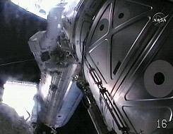 In an image taken from a NASA video, astronaut Tim Kopra, top left, embarks on the first spacewalk by the crewmembers of the shuttle Endeavour, as seen from the helmet cam of fellow astronaut Dave Wolf.