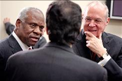 The issue has been discussed repeatedly, says Justice Clarence Thomas, left. Justice Anthony Kennedy, right, says cameras would invite competition for sound bites.