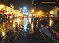 A man sleeps on a bench Monday after it rained in Iquique, Chile.  Roofs were damaged and power was knocked out.
