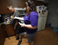 Michelle Briggs helps her husband Bob sort his medication in their home on July 15 in Hillsboro, Iowa. Briggs gave up her job as a veterinarian technician to care for the former Army sergeant and their two kids.