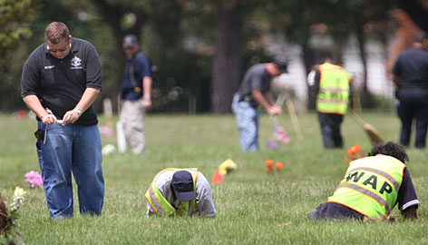 Searchers painstakingly look for remains at the Burr Oak Cemetery in Alsip, Ill., near Chicago, where as many as 300 graves were discovered to have been disturbed. The cemetery has been closed since July 10. About 200 pieces of bone and fragments have been recovered so far.