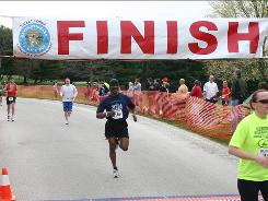 Michael Solomon, a veteran runner with the Back on My Feet group, crosses the finish line of a 5 mile race in Valley Forge Park.