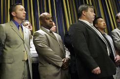Cambridge Police Sgt. James Crowley, far left, listens as a multiracial group of officers and union leaders, including Cambridge Police Patrol Officers Union President Steve Killion, foreground right, hold a news conference in Cambridge, Mass., on Friday to show support for Crowley, who was the arresting officer of Harvard professor Henry Louis Gates at his home on July 16.