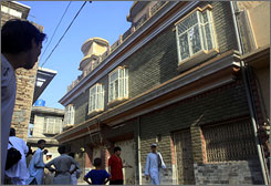 Local residents gather outside the house of Pakistani pro-Taliban cleric Sufi Muhammad after his detention in Peshawar.