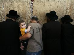 A Jewish man holds a child during morning prayers before the beginning of Yom Kippur at the Western Wall, Judaism's holiest site in Jerusalem. Prayers on papers can be seen stuffed into the cracks.