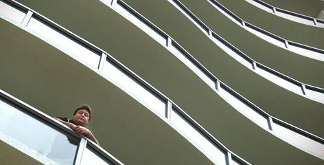 Victor Vangelakos, a New Jersey firefighter, looks down from his seventh-floor balcony in a 32-story high-rise in Fort Myers, Fla., where he and his family are tired of being the sole occupants.