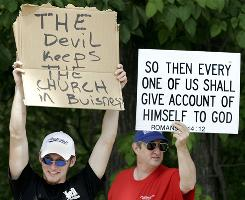 "In Hell, Mich., people hold signs on June 6, 2006 (aka 6/6/06). According to the Bible's Book of Revelation, ""666"" is the mark of the beast. The Book of Revelation also describes hell as a lake of fire."