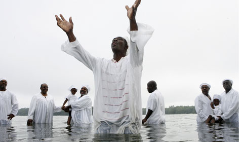 Michael Owens, pastor of New Hope Baptist Church, preaches during baptism Sunday in Lake Providence, La.