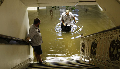 Library workers Joe Brady, left, and William Cantelli wade through floodwaters in the basement of a library in downtown Louisville. Thousands of books were damaged.