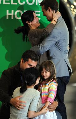 Freed U.S. journalists Laura Ling, top, embraces her husband Iain Clayton, while Euna Lee is welcomed by husband Michael Saldate and daughter Hanna after they arrive from North Korea at the airport in Burbank, Calif., with former president Bill Clinton on Wednesday.
