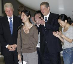 Laura Ling, left, and Euna Lee, two American journalists who were arrested in March after allegedly crossing into North Korea from China, are joined by former president Bill Clinton and former vice president Al Gore at Bob Hope Airport in Burbank, Calif., on Wednesday.