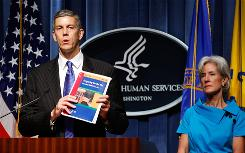 "Secretary of Education Arne Duncan holds up a copy of ""Preparing for the Flu,"" a toolkit for K-12 schools, as Health and Human Services Secretary Kathleen Sebelius looks on Friday."