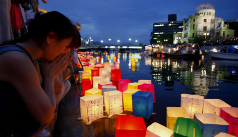 A woman offers prayers as she releases a paper lantern in the Motoyasu River near the Atomic Bomb Dome in Hiroshima.