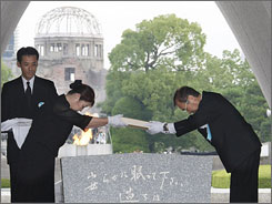 Mayor Tadatoshi Akiba, right, offers a new list of atomic bomb victims Thursday during the 64th anniversary ceremony at Hiroshima Peace Memorial Park.