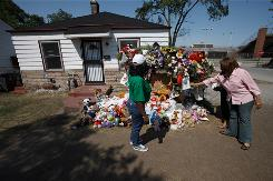 Cheryle Grace, right, and Valerie Grace visit the growing memorial at Michael Jackson's childhood home in Gary, Ind., at 2300 Jackson St.