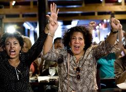 Carmen Vasquez, left, and Eve Valenquela react to the announcement of the Senate's confirmation of Sonia Sotomayor as Supreme Court justice Thursday at East Harlem's FB Lounge, a popular Puerto Rican hangout.