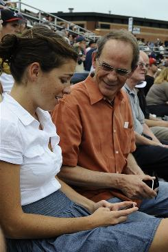 "Dave Hesel, 62, and daughter Kate Hesel, 27, whip out their iPhones at the Lowell Spinners minor league baseball game at Edward LeLacheur Park in Lowell, Mass. Kate says technology is ""second nature"" for her generation, but ""less fluid"" for her parents' generation."