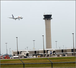 A plane lands at Memphis International Airport in September 2007 with the air traffic control tower in the background.
