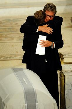 Ted Kennedy Jr., with glasses, and Patrick Kennedy hug at the funeral of Sen. Edward Kennedy on Aug. 29. The brothers are promoting their father's memoirs, which came out Monday.