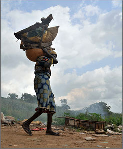 A woman carries a load of goods as she walks through the Abuja neighborhood in Lagos, Nigeria, in June.