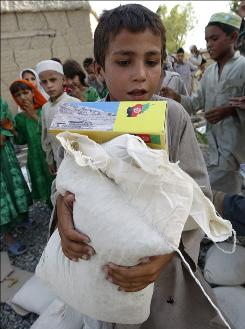 A boy carries humanitarian aid distributed by the U.S. army at the village of Doment, in Afghanistan's Kunar province, on Aug. 16.