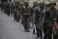 Soldiers patrol the streets in Tegucigalpa Friday while supporters rally on behalf of ousted Honduran President Manuel Zelaya. The U.S. military on Saturday denied its troops assisted or knew of the June flight that took Zelaya into exile during a coup.