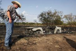 Bosque County Sheriff Anthony Malott points to the charred remains of a car whose catalytic converter likely started a 30-acre grass fire in Steele Creek, Texas, in late July. The driver died.