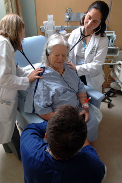 Doug Dreffer, MD, kneeling, talks with patient Erma Hodgman as residents Anne Barry, DO, left, and Melissa Buddensee, MD, check her breathing during rounds at Concord (N.H.) Hospital. Experts predict the U.S. will be 40,000 doctors short by 2020.
