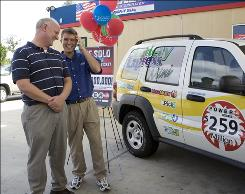 Murphy USA store manager Drew Evans, right, and district manager Joe Lewis react to all the attention at the Columbia, S.C., store that sold the winning Powerball ticket.