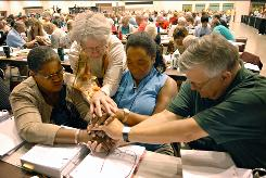 Evangelical Lutheran Church of America voting members, from left, Orinda Hawkins-Brinkley, Diane Yeager. Marj Ellis and Steven Schnittke, along with other members of the ELCA, stop for a moment of prayer Friday at the Minneapolis Convention Center. More than 1,000 members debated and voted on whether to allow gay and lesbian clergy to serve while be in committed same-sex relationships.