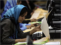 An election worker counts votes at the Independent Election Commission in Kabul.