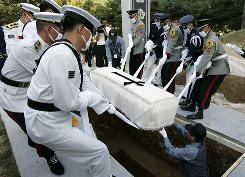 Honor guards and workers lower the coffin of former South Korean president Kim Dae Jung into the ground at his state funeral on Sunday in Seoul.