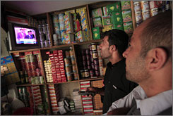 A shop owner and patrons tune into listen to the Afghan Independent Election Commission.
