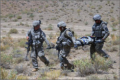 Army infantry troops carry a wounded soldier who was injured when rolling over a mine in Zabul Province, Afghanistan, on Friday. The soldier is to be medically evacuated.