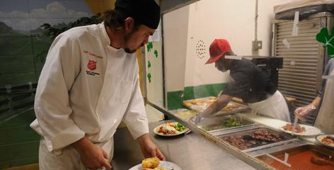 Salvation Army chef Timothy Tucker, 33, helps with expediting of lunch plates in Louisville. The food is locally produced or harvested from their own on-site organic garden.