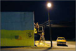 Winfred Mize of Starr, S.C., paints a mural for Planet Hotdog under a streetlight.