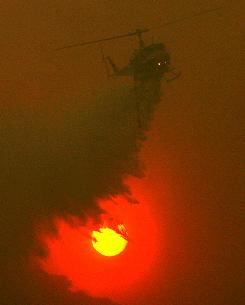 A helicopter drops water on hot spots as it flies through dense smoke near Acton, Calif.
