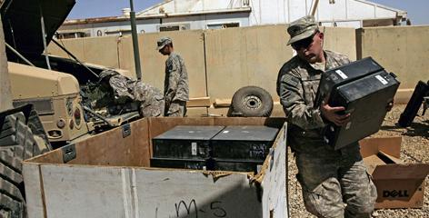 U.S. Army Spc. Shawn Byrd packs up computer equipment at Camp Victory, in Baghdad, for shipping to Afghanistan.