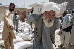 An Afghan man carries a sack of wheat to distribute to displaced families in Kandahar in May. More than 130 displaced families receive the food from the World Food Program.