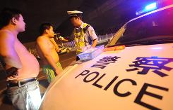 An officer conducts a breathalyzer test at a road block in Beijing on Aug. 15. Chinese police are cracking down on drunken drivers as more than 1,200 new cars hit the roads of China's capital every day, on average.