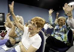 At a local town-hall-style meeting last month, Marilynn Garfield of Delray Beach, Fla., left, raises her hand as part of an informal audience tally of those who have Medicare coverage.