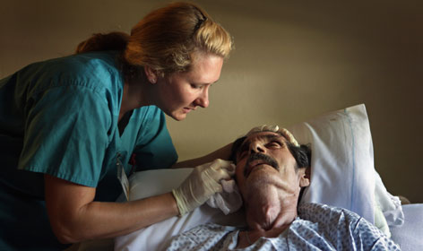 Registered nurse N. Von Reiter comforts a man at the Hospice of Saint John in Lakewood, Colo. Health care, a field traditionally dominated by women, is one part of the economy that is still growing.