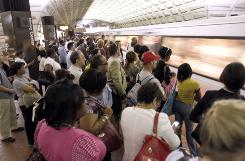 Commuters await a Red Line train at the Metro Center station in Washington on June 25.