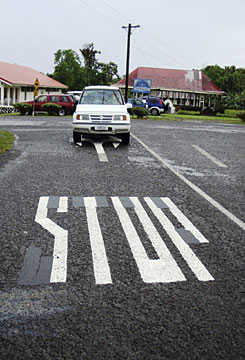 A car drives against a traffic sign painted on a road in central Apia, Samoa, on Sunday, a day before driving sides switch.