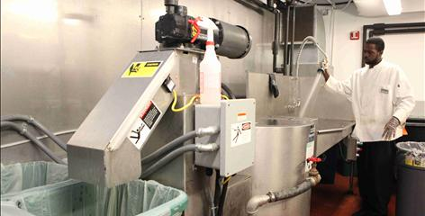 Pulp it up: Brandon Taliaferro puts the House's cafeteria waste into a pulping machine, which reduces its volume by 90% and its weight by as much as 50%.