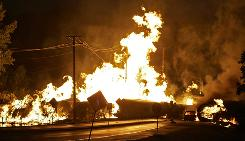An automobile, right, and rail cars loaded with ethanol are engulfed in flames after the train derailed in Rockford, Ill., on June 19.