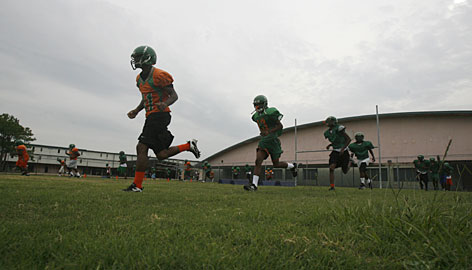 The Carver High School football team practices in front of their old school, which was ravaged by Hurricane Katrina in 2005.