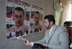 Dargham al-Zeidi puts up a poster of his brother, Muntadhar al-Zeidi,  in preparation for his release from jail for throwing his shoes at then president George W. Bush.