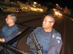 City officers Osiel Rojas, left, and Rafael Trujillo patrol Uruapan, Mexico, from a truck. Mexico's federal government is giving local cops new equipment and training to fight cartels.