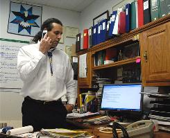 Cheyenne River Sioux Tribe attorney Tom Van Norman talks on the phone about the tribe's lawsuit against the local school district in his office in Eagle Butte, S.D.